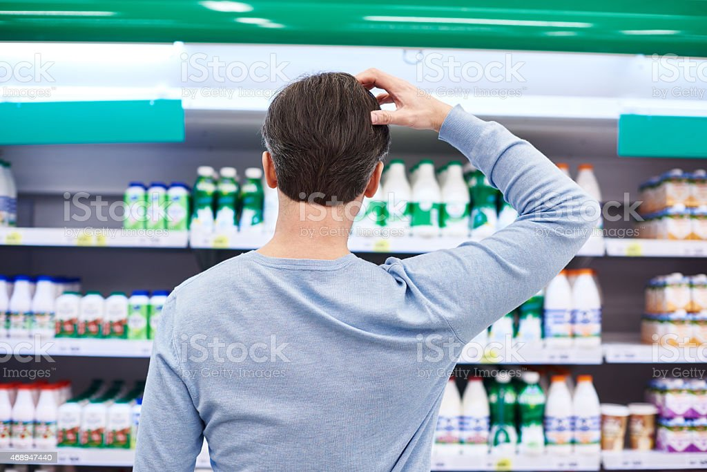Man chooses dairy products in store stock photo