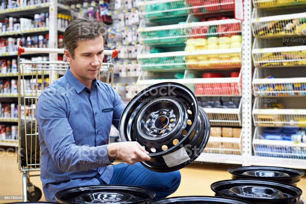Man chooses disks for car in store. stock photo