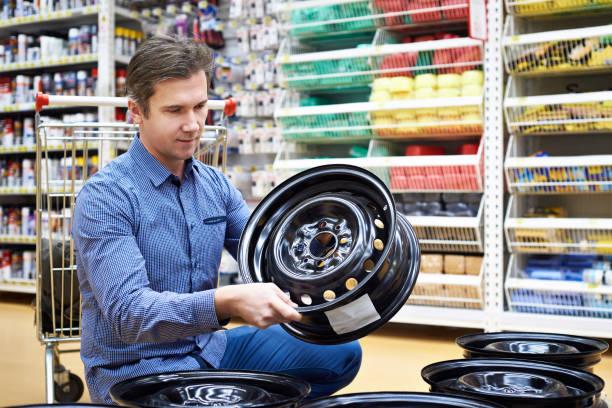 Homem escolhe discos para o carro na loja. - foto de acervo