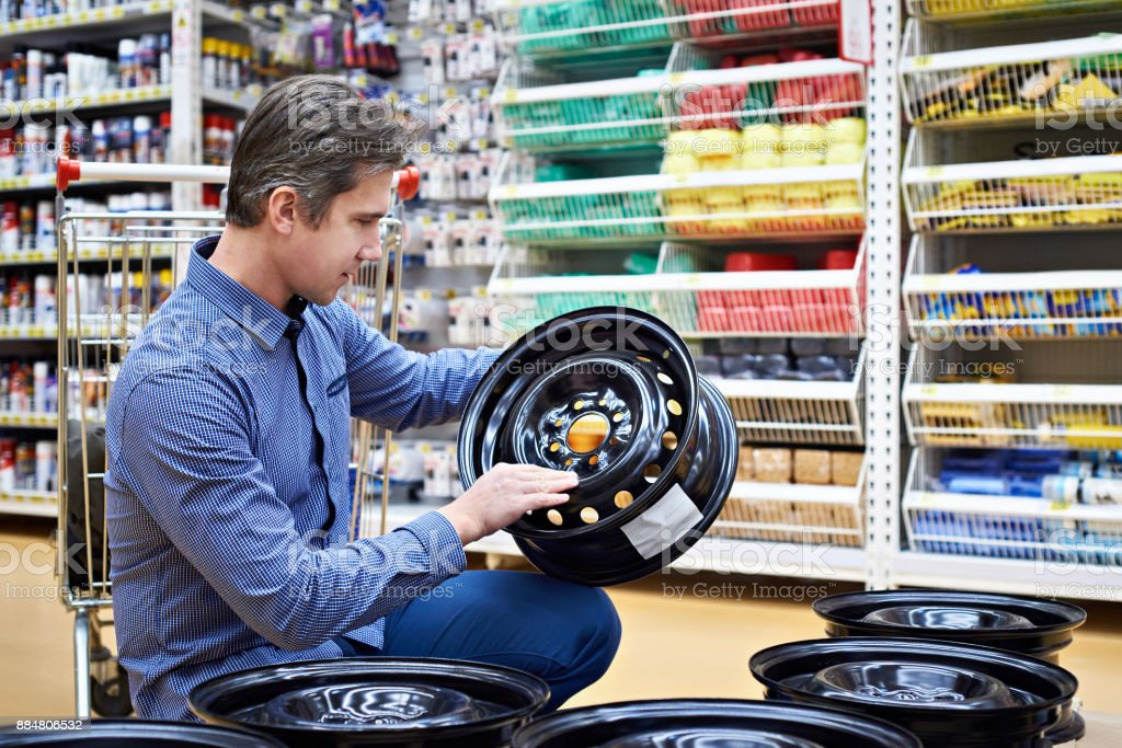 Man chooses disks for car in store stock photo