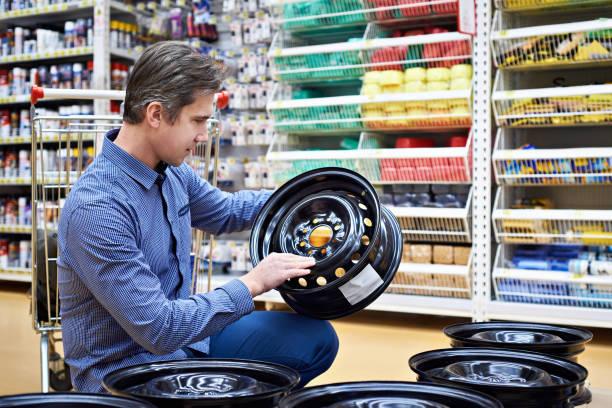 Homem escolhe discos para o carro na loja - foto de acervo