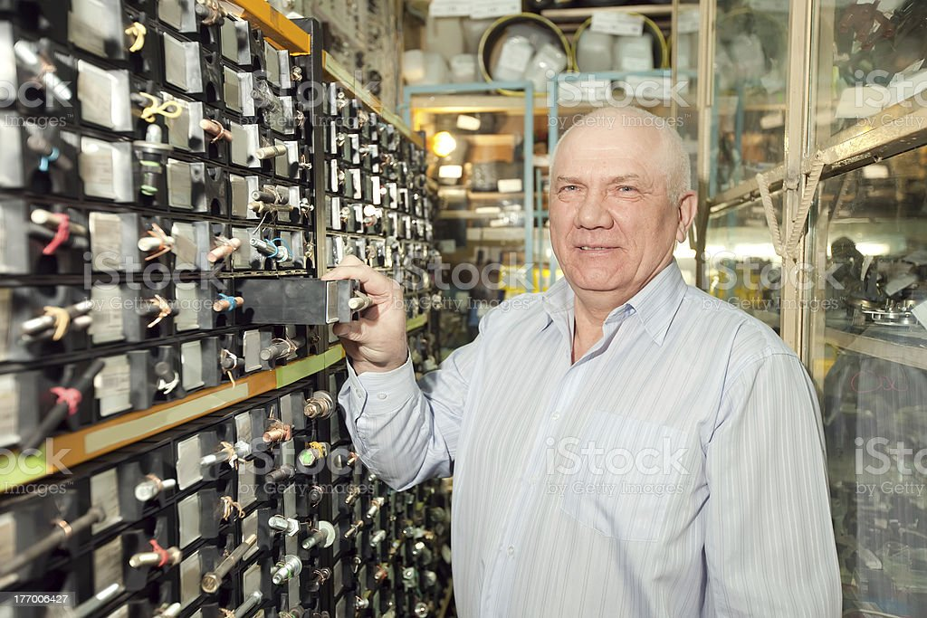 man chooses fasteners in  auto parts store stock photo