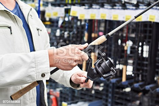 istock Man chooses fishing rod in shop 970448968