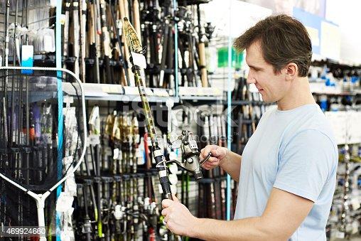 istock Man chooses fishing rod in sports shop 469924660