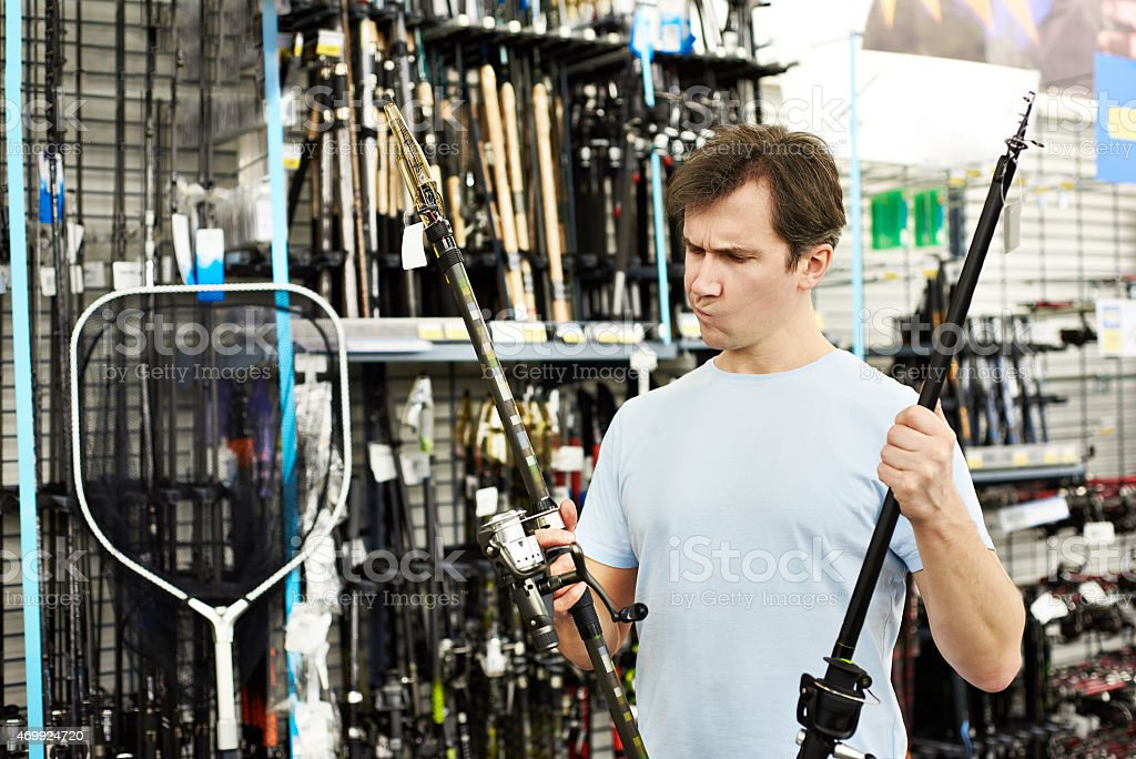 Man chooses fishing rod in sports shop stock photo