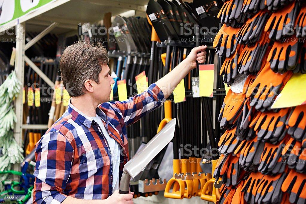 Man chooses shovel in shop stock photo