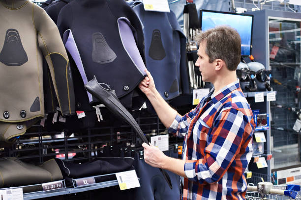 Man chooses wetsuit and fins for spearfishing in sports shop Man chooses a wetsuit and fins for spearfishing in a sports shop wetsuit stock pictures, royalty-free photos & images