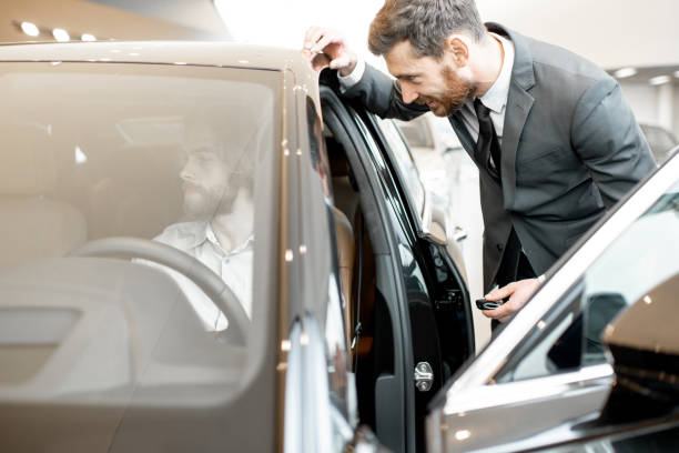 Cтоковое фото Man choosing a new car with salesperson in the showroom