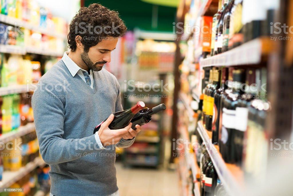Homem escolher uma garrafa de vinho - fotografia de stock