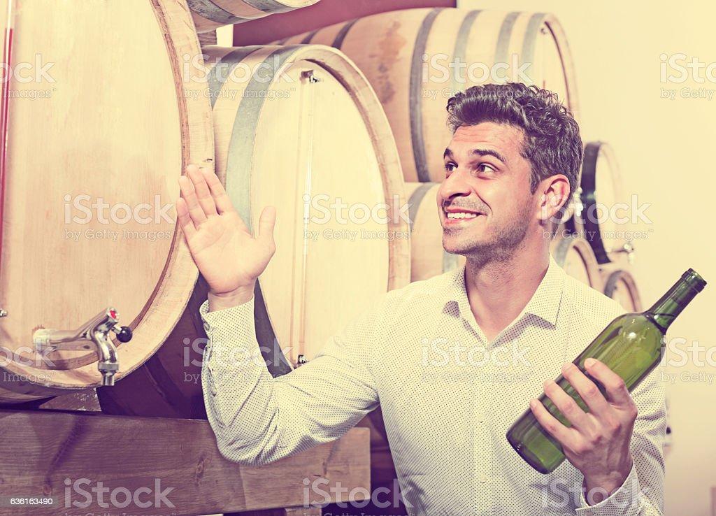 man choosing bottle of wine in shop stock photo