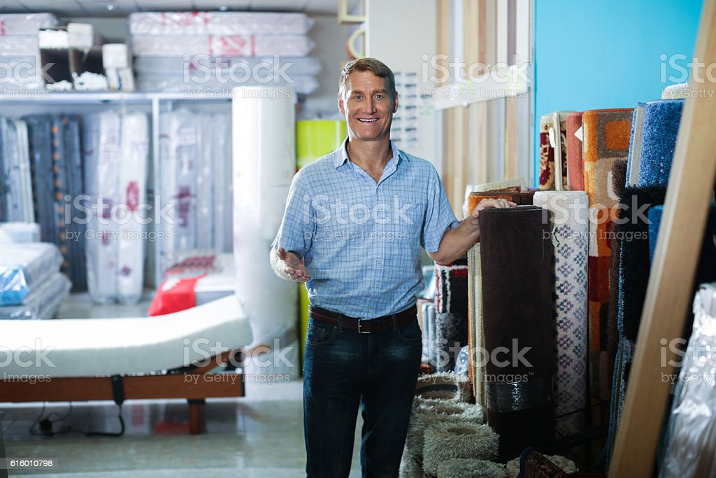man  choosing carpets in household department stock photo