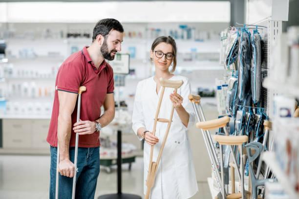 mann, die krücken in die apotheke zu wählen - orthopädisches hilfsmittel stock-fotos und bilder