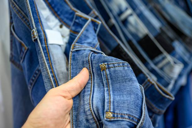 Man choosing jeans the shop stock photo