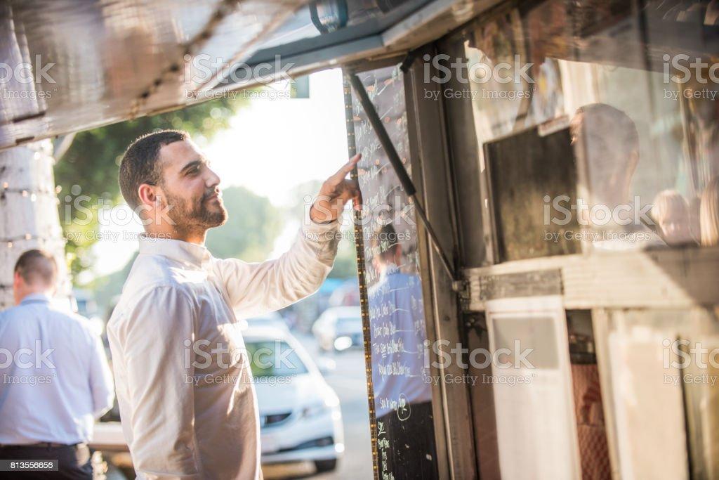 Man Choosing Meal from Menu off Food Truck stock photo