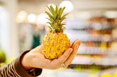 Man choosing mini pineapple in grocery store