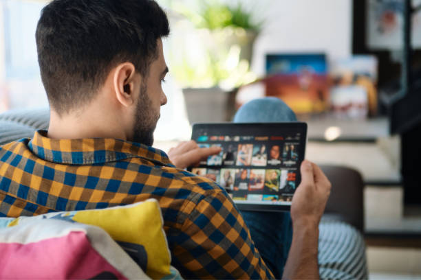 Man Choosing Movie For Streaming On Tablet Computer stock photo