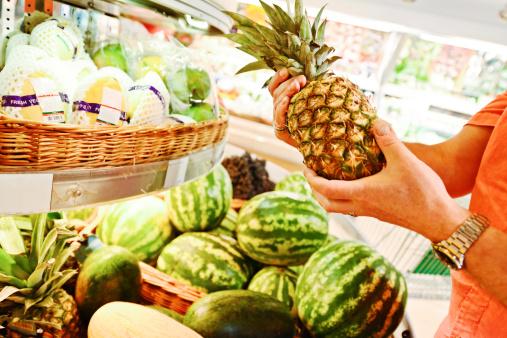 Man choosing pineapple in grocery store