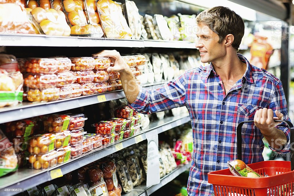 Man Choosing Product On Shelf While Shopping In Supermarket stock photo
