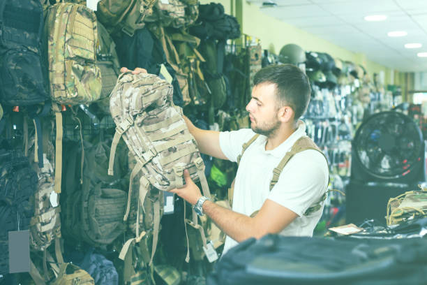 Man choosing textile backpack gun in military shop stock photo
