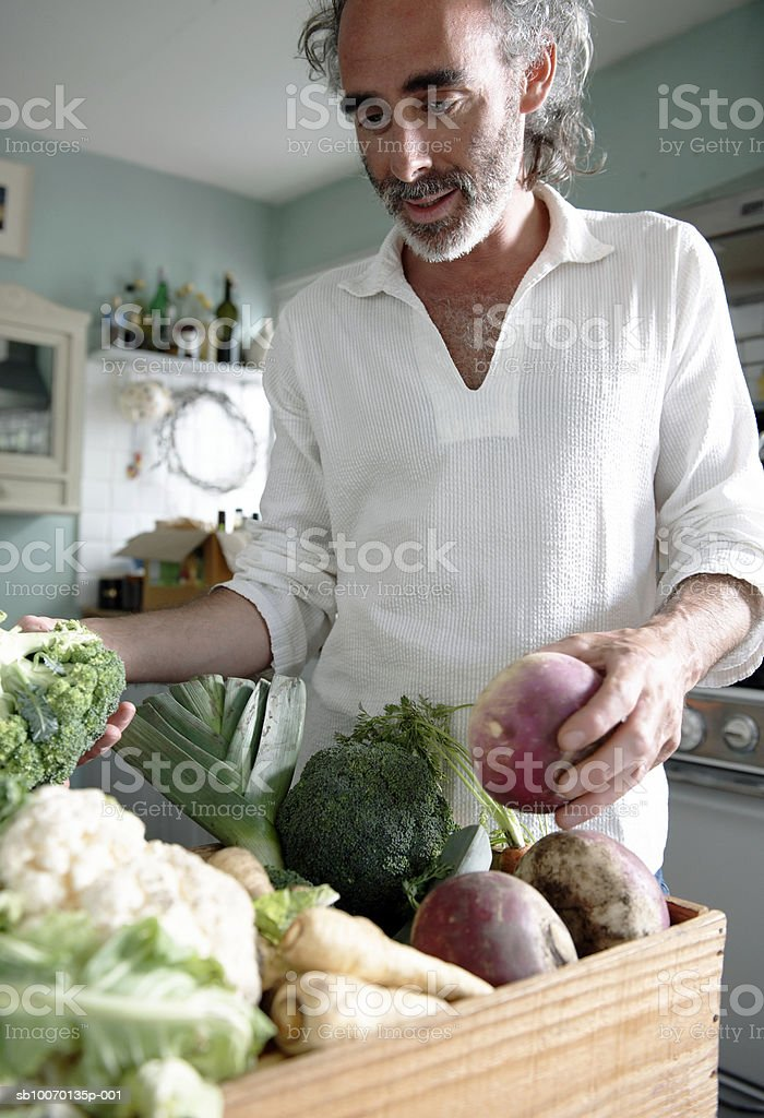 Man choosing vegetables from crate in kitchen royalty-free stock photo