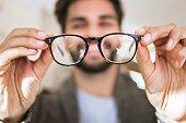 Man choosing glasses in optical store using mirror