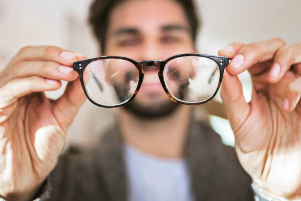 man choosing wearing glasses in optical store - eyewear stock pictures, royalty-free photos & images