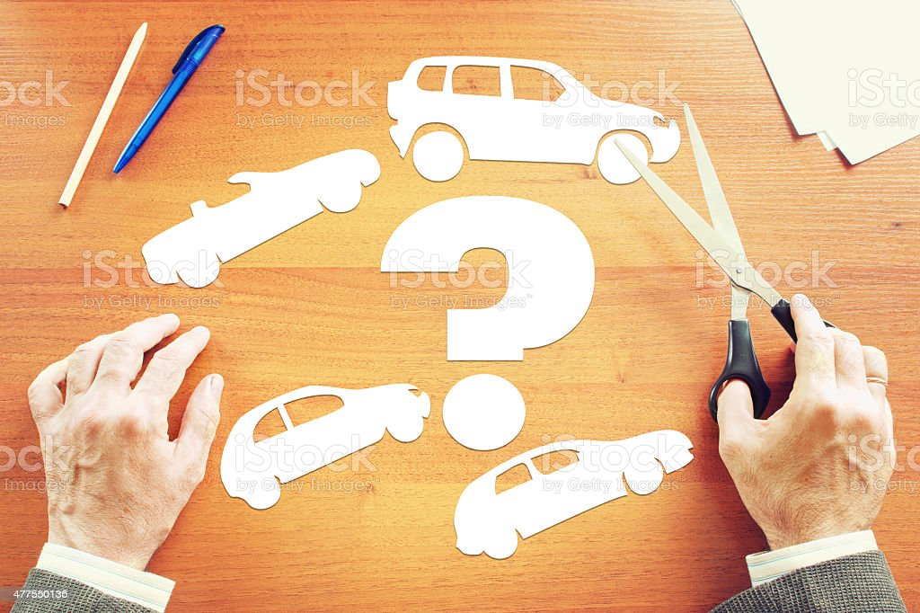 Man choosing which kind of car to buy stock photo