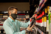 istock Man choosing wine in a grocery store and using face mask 1252794962