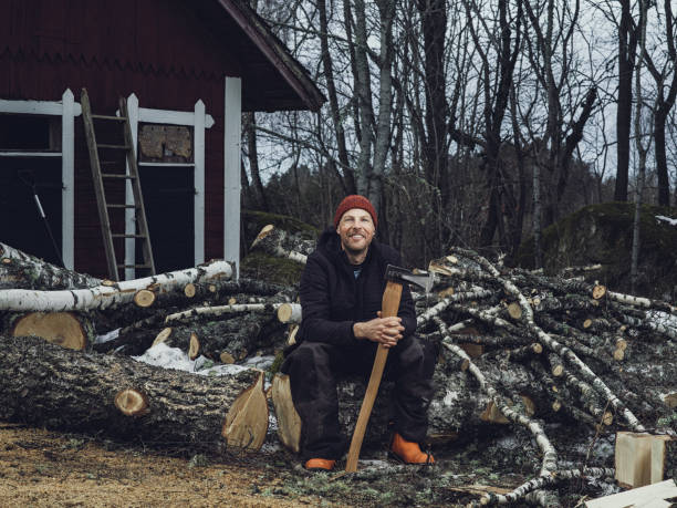 Man chopping cleaving doing wood work outside woodcutter/lumberjack Man chopping cleaving with axe doing wood work outside woodcutter/lumberjack Man shopping up a tree in fire wood size, photo taken outdoors forester stock pictures, royalty-free photos & images
