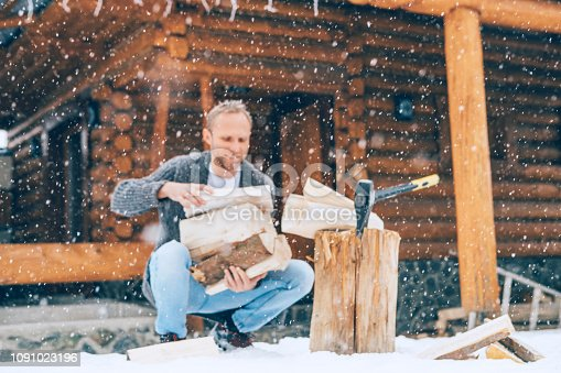 Man chopping wood on snowy yard for a house fireplace with heavy snowflakes background . Winter countryside holidays concept image