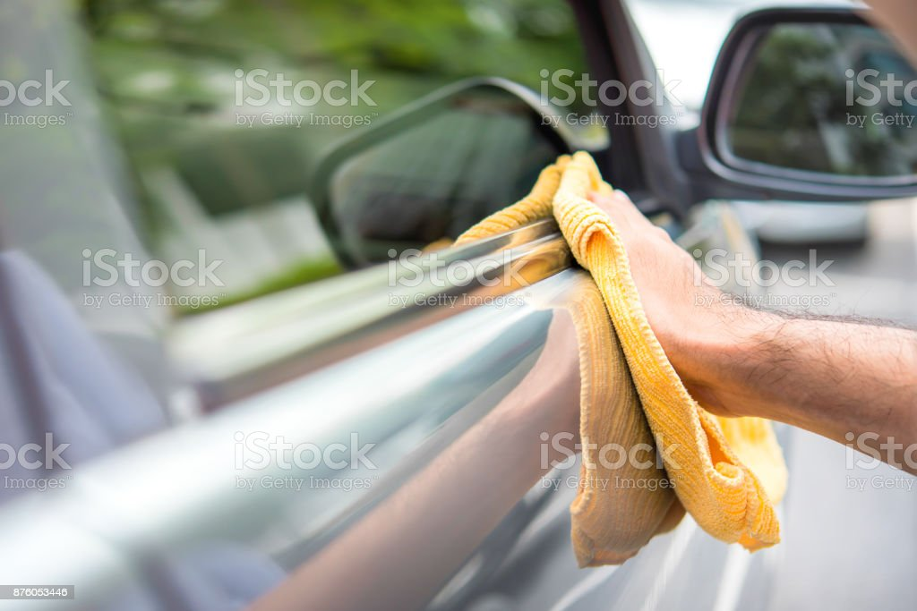 A man cleaning a car with yellow microfiber cloth - car detailing, vale and auto service concept foto stock royalty-free