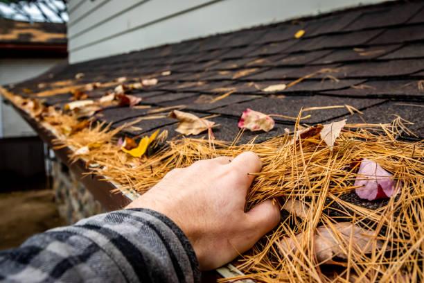 een man het schoonmaken van een dak goot. - foto's van hands stockfoto's en -beelden