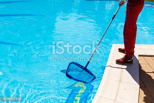 Man cleaning a swimming pool in summer with a brush or net on a blue pole standing barefoot on the tiles at the edge, low angle view of his lower body.