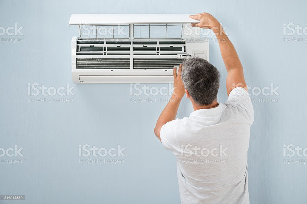 Man Cleaning Air Conditioning System stock photo