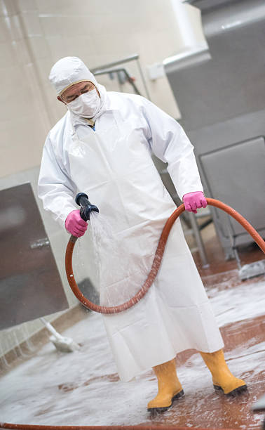 Man cleaning at a factory Man cleaning machines at a factory with a hose and wearing full uniform food warehouse stock pictures, royalty-free photos & images