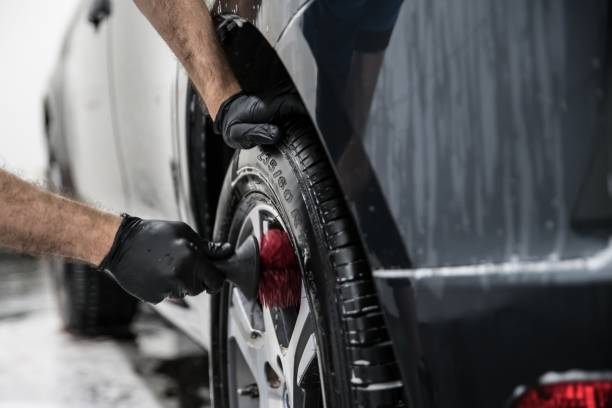 Man cleaning car wheel with brush. stock photo