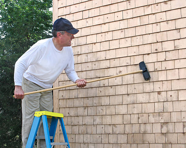 Man cleaning cedar shingles stock photo
