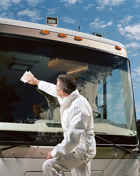 Man cleaning coach bus windshield, side view stock photo