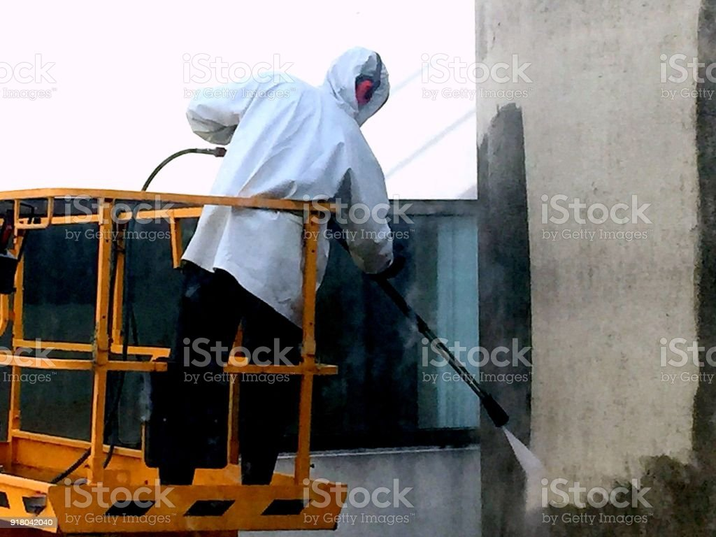 Man cleaning concrete using high-pressure water stock photo