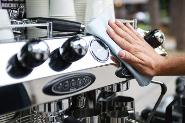 Man cleaning espresso machine after working day stock photo