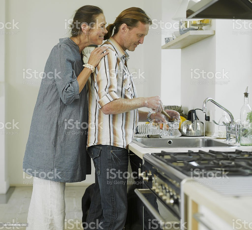 Man cleaning glasses, woman watching from behind, side view 免版稅 stock photo