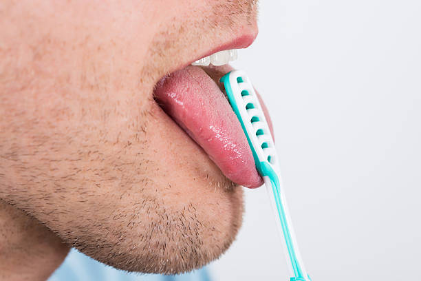 man cleaning her tongue - mensentong stockfoto's en -beelden