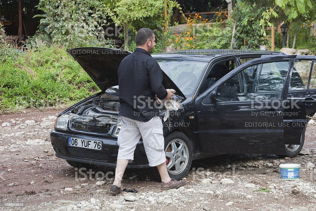 Man cleaning his car after flood disaster stock photo