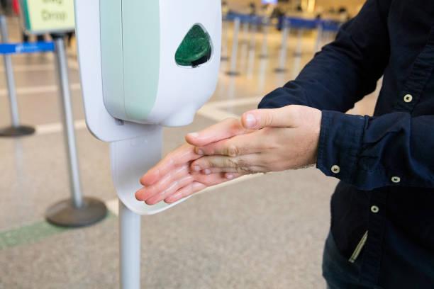 Mann reinigt seine Hände mit Sanitizer Spender mit Alkoholgel am Flughafen – Foto