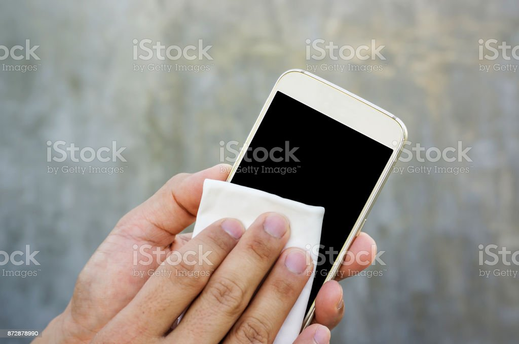 Man cleaning his smartphone with a microfiber cloth. stock photo