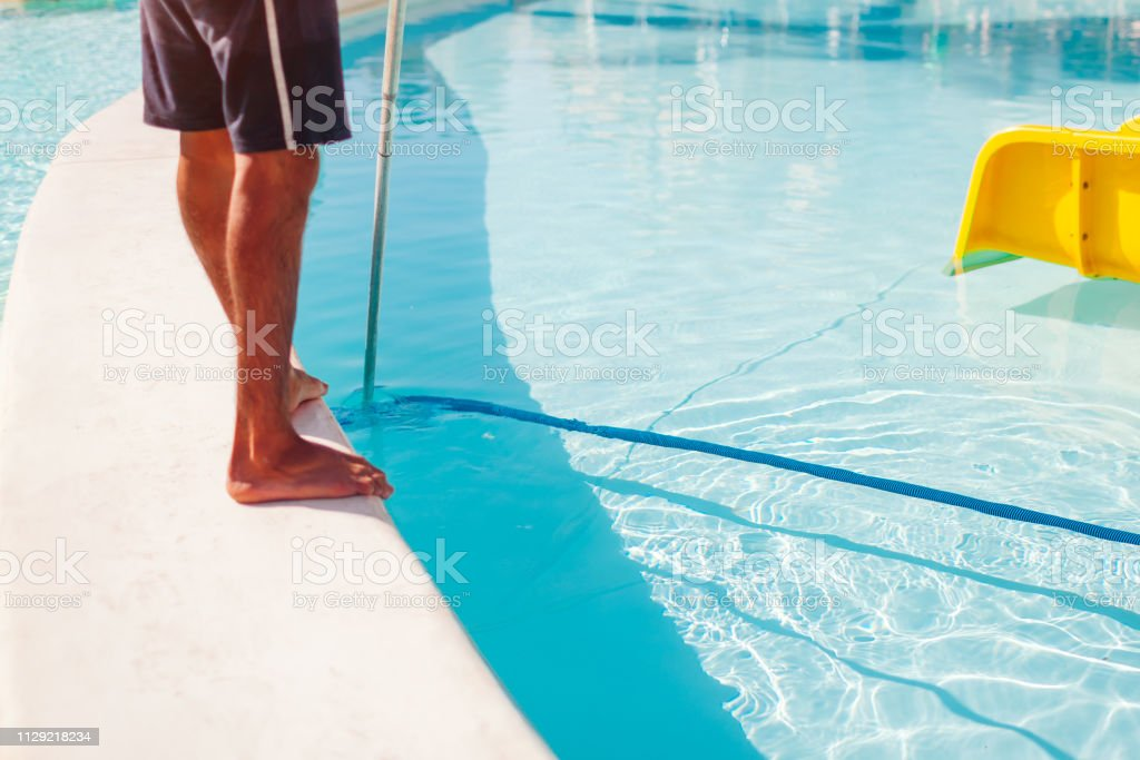 Man Cleaning Hotel Swimming Pool With Vacuum Tube Cleaner In ...