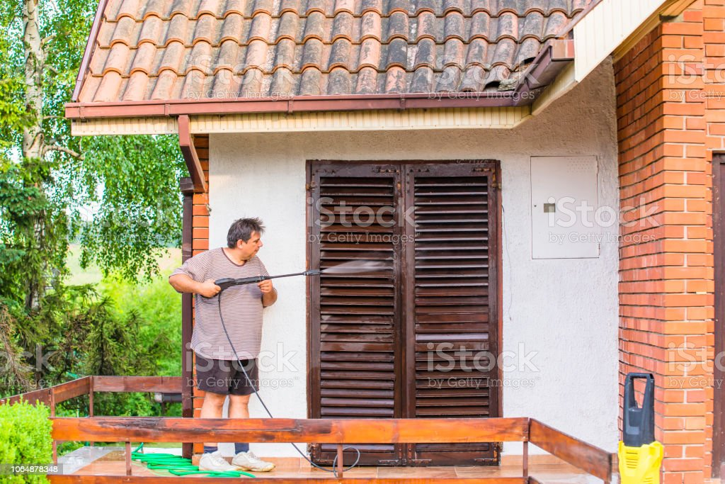 Man Cleaning House With Water Spray Stock Photo & More