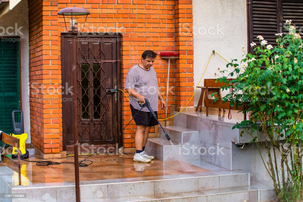 Man Cleaning House With Water Spray Stock Photo - Download