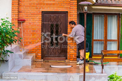 Mid Aged Manual Worker Cleaning Building Exterior with Water Hose and Spray