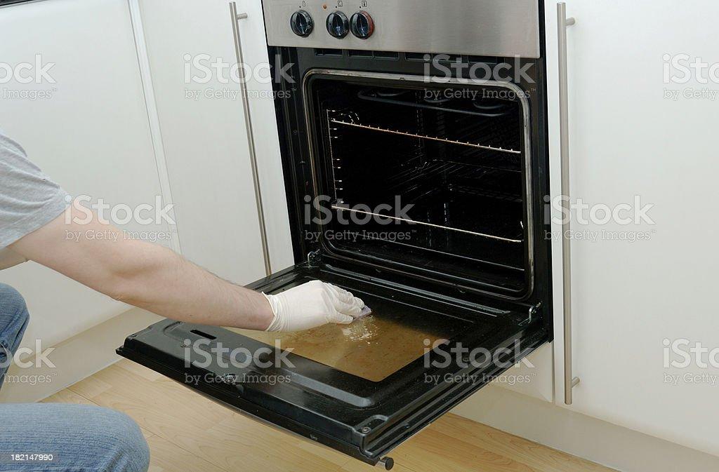 Man cleaning kitchen oven stove door stock photo